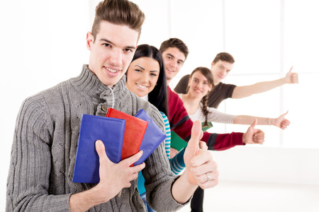 back up: Group of cheerful students with books standing In A Row with thumb up in school hall and looking at camera.