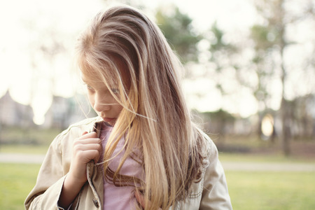 shy girl: Close-up of a little girl standing alone outside with a sad expression on her face looking to the side. Stock Photo
