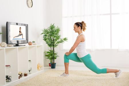 ejercicio aer�bico: Joven y bella mujer estirando las piernas en casa delante de la tv