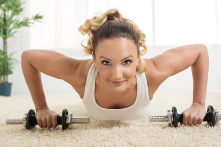 pushup: Beautiful young woman doing push-up at home. Looking at camera. Close-up. Stock Photo