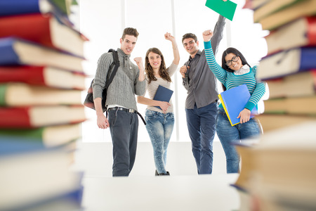 Group of cheerful students standing among the books with arms raised in a fist in school hall and looking at camera.