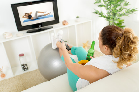 perezoso: Mujer perezosa en ropa deportiva sentado frente al televisor y no acostumbra a hacer ejercicio.