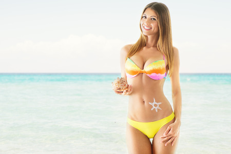 thin shell: Attractive girl in a bikini, on the beach, holding a shell. Looking at camera. Stock Photo
