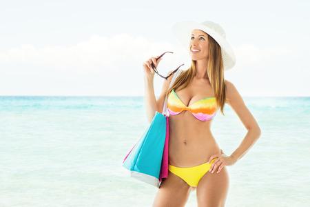 sun hat: Attractive girl in bikini with Sun Hat on the beach holding beach bag.