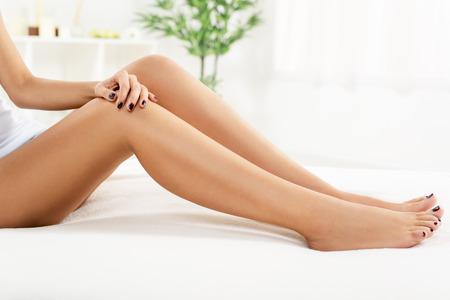 piernas: Mujer joven con las piernas perfectas sentarse y relajarse en casa.