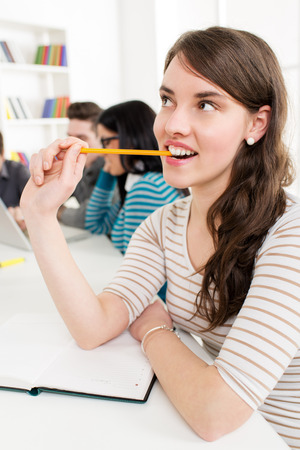A beautiful smiling girl learning, Biting her pencil and thinking in the foreground. A happy group of her friends is behind him and looking at laptop. photo