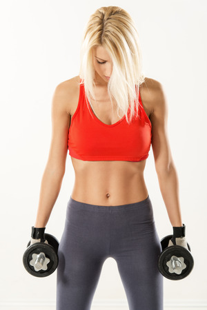 Cute young woman standing and holding dumbbell. She is preparing at doing exercise. White background.