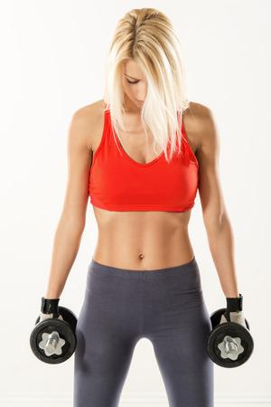 haciendo ejercicio: Mujer joven linda de pie y sosteniendo mancuernas. Ella se est� preparando a hacer ejercicio. Fondo blanco. Foto de archivo
