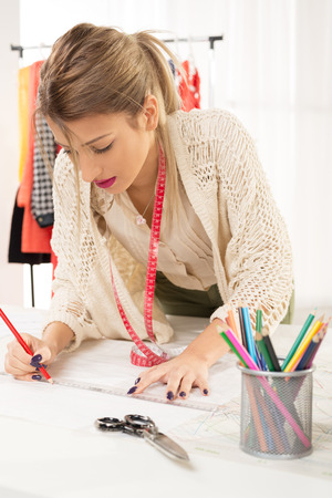 sewing pattern: Young woman, fashion designer, with tape measure draped over the neck, drawing with a ruler on sewing pattern. Stock Photo