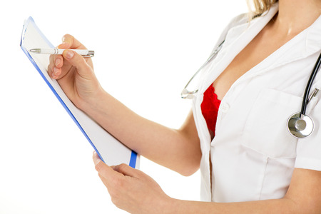 Cropped image of a sexy nurse filling in forms on white background. Stock Photo