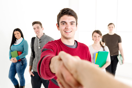 sucessful: A young sucessful man student with books is standing in the foreground and shaking hand. A group of his friends is behind her. Looking at camera.
