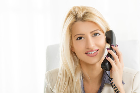 phoning: Close-up of a young beautiful businesswoman phoning and looking at the camera. Stock Photo