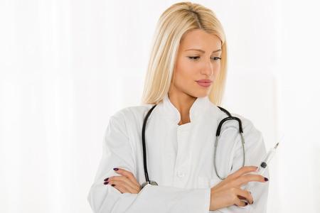 bata blanca: Mujer joven bastante rubia en una bata blanca, con un estetoscopio en el cuello que celebra una inyecci�n. Foto de archivo