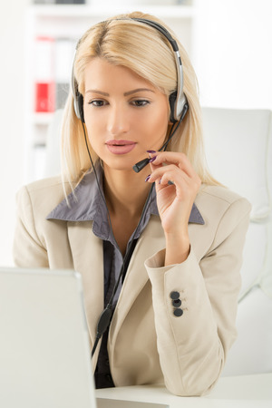handsfree device: Young beautiful blonde girl, elegantly dressed, sitting at an office desk in front of laptop with a headset on her head.