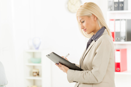 Young beautiful businesswoman standing in office, holding folder and working. In the background you can see the shelves with binders.