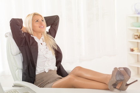 at her desk: Young pretty successful businesswoman in the office sitting on chair, hands behind  head with her feet up on a desk. She is relaxing and daydreaming. Stock Photo