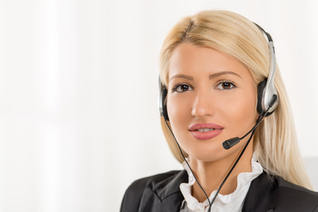 handsfree device: Close-up of a portrait young beautiful blonde girl, elegantly dressed, sitting at an office with a headset on her head. With a smile looking at the camera.