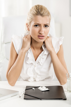 Young beautiful exhausted businesswoman sitting in the office, holding her neck with a pained expression on her face looking at the camera. In front of her on her office desk are documents and pills. photo