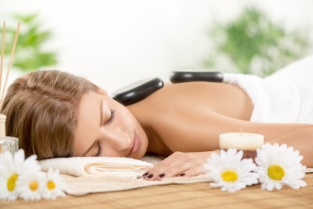 lastone: Young beautiful woman relaxing at spa centre. She is enjoying at stone massage.