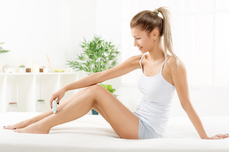 electric razor: Young beautiful woman depilation leg with Electric Razor.