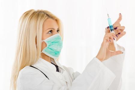 bata blanca: Mujer joven bastante rubia en una bata blanca, con un estetoscopio sobre la celebraci�n del cuello y la preparaci�n de una inyecci�n. Foto de archivo