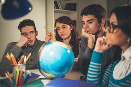 Four beautiful students of Geography learning with globe and thinking. Vintage concept. Фото со стока
