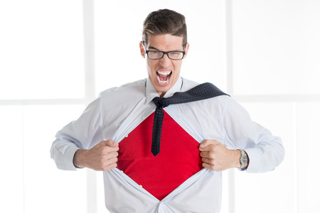 ripping shirt: Angry businessman ripping open his shirt and exposing a Superhero red costume underneath. The man is wearing glasses and looking at camera.