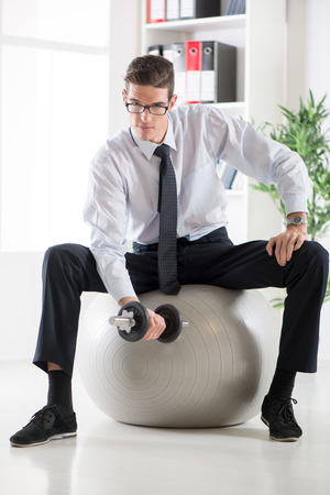 mannen pak: The young businessman sitting in the office on pilates ball and doing exercise with dumbbells.