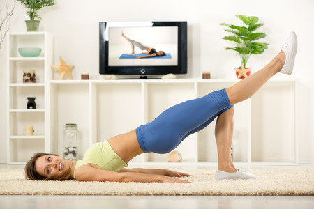 home interior: Young woman in sports clothes, doing exercises in the room, in front TV.