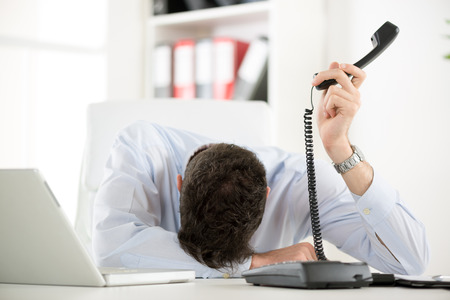 front desk: A young tired businesswoman, exhausted from work sleeping in front of his laptop, leaning on office desk with a telephone handset on hand.