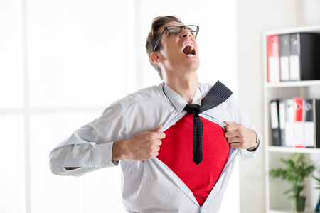 angry person: Angry businessman ripping open his shirt and exposing a Superhero red costume underneath. The man is wearing glasses.