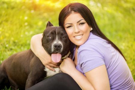 stafford: Giovane e bella donna abbraccia il carino stafford terrier. Si siede sull'erba nel parco e godersi. Guardando cemera.