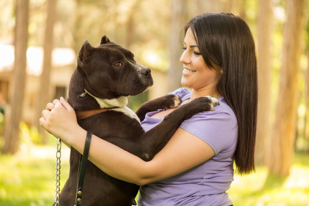 stafford: Beautiful young woman with her cute stafford terrier hugging in the park. Stock Photo