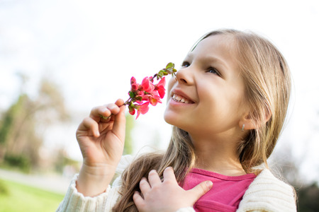 smelling: Smiling cute little girl smelling spring flower in the park.