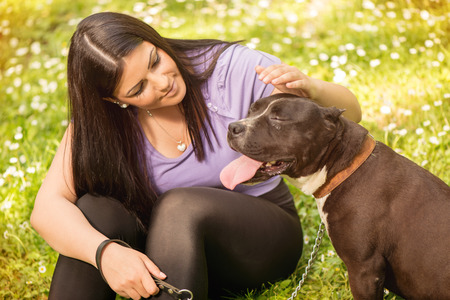 stafford: Beautiful young woman with her cute stafford terrier sitting on grass in the park and enjoying. Stock Photo