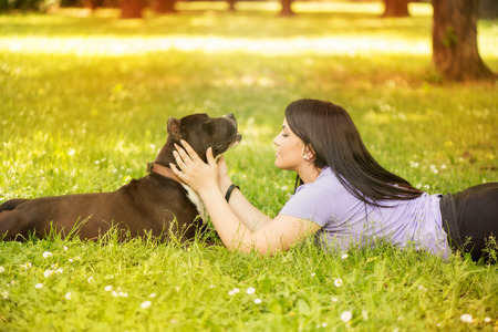 stafford: Beautiful young woman with her cute stafford terrier lying on grass in the park.