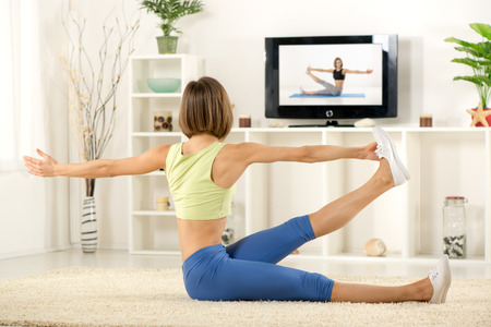 Young woman in sports clothes, doing exercises in the room, in front TV.
