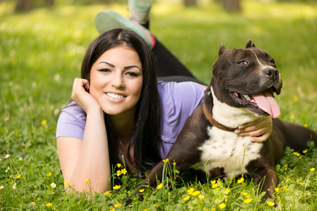 stafford: Beautiful young woman with her cute stafford terrier lying on grass in the park. Looking at camera.
