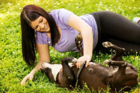 stafford: Giovane e bella donna che gioca con la sua cute terrier Stafford nel parco.