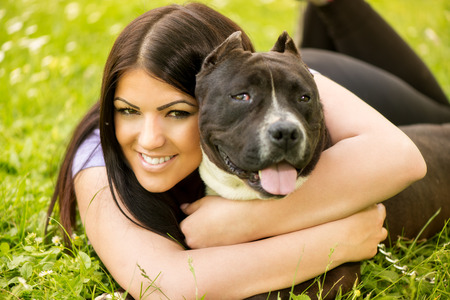 stafford: Beautiful young woman with her cute stafford terrier lying on grass in the park and hugging. Stock Photo