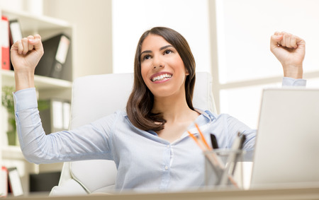 Successful businesswoman sitting at the desk in the office with raised arms and celebrating success. photo