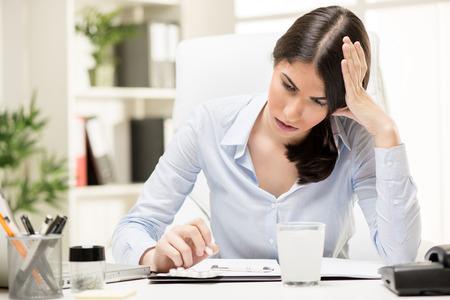 empleado de oficina: Empresaria hermosa joven en el trabajo, sosteniendo su cabeza con una expresi�n de dolor en su rostro mirando las p�ldoras en su escritorio de oficina. Foto de archivo
