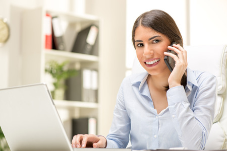 phoning: Portrait of a beautiful young businesswoman sitting in the office and phoning at mobile phone. Looking at camera. Stock Photo