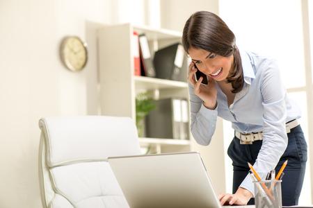 secretaria: Empresaria ocupada Hermosa, de pie ofiice, con un ordenador portátil y hablando por teléfono móvil.