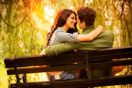 Vue arrière d'un jeune couple dans l'amour assis sur un banc de parc, éclairé par la lumière du soleil, regard passionné les uns les autres dans le moment avant de le baiser.