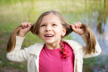funy: Beautiful funy little girl enjoying in the park in spring.