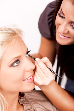 Make-up artist applying makeup on beautiful woman