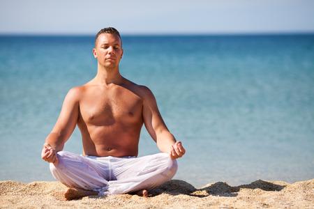 man meditating: Young man meditating on the beach