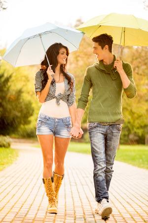 uomo sotto la pioggia: Giovane coppia in amore con ombrelloni mentre si cammina sotto la pioggia attraverso il parco per mano e guardarsi l'un l'altro con un sorriso.