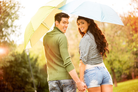 holding hands while walking: Rear view of a young couple in love with umbrellas while walking in the rain through the park holding hands and looking at camera other with a smile. Stock Photo